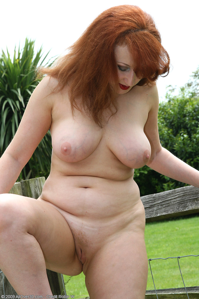 Curvy redheaded cougar playing with her hairy pussy